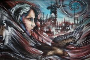 street art of a woman, bird and wolf against an urban skyline