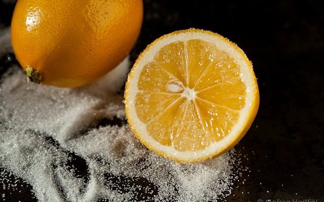 Cut in half lemon in a pile of sugar